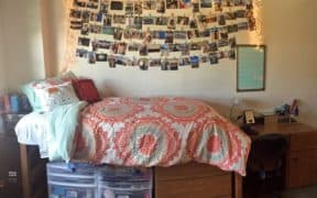 dorm bed with hanging pictures