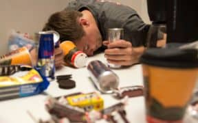 man passed out holding energy drink