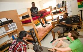 happy college roommates laughing in dorm room
