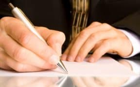 man writing recommendation on paper